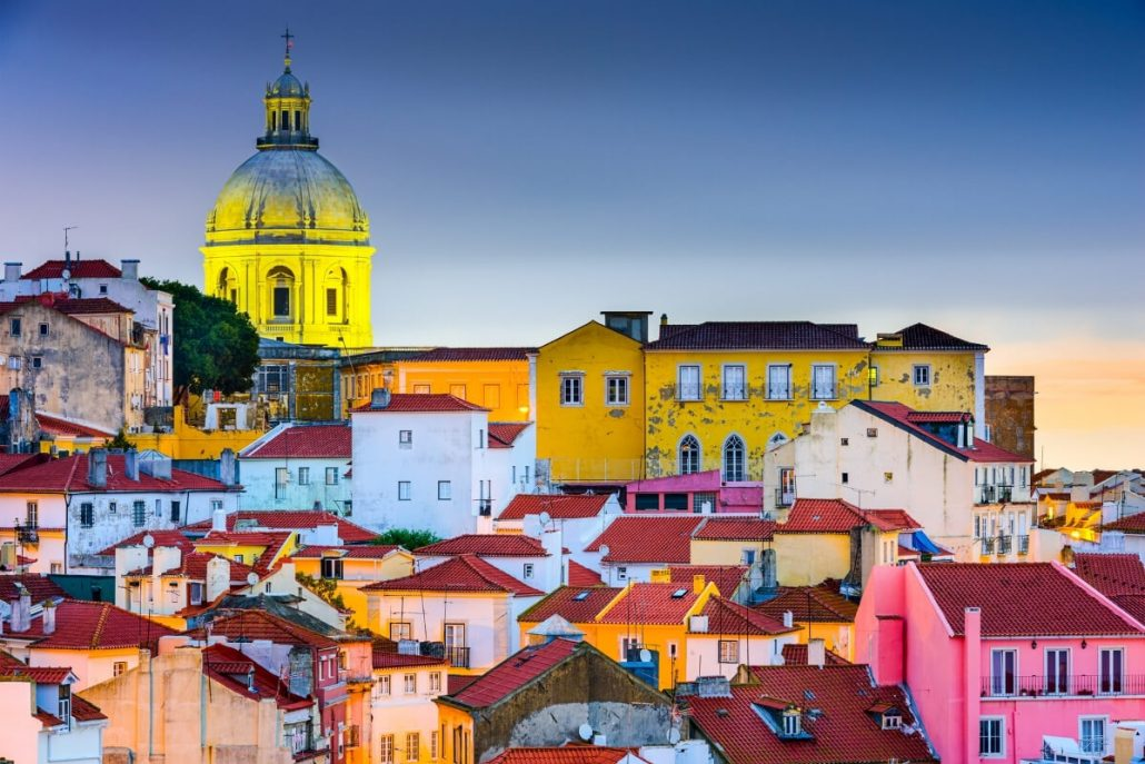 A picture of a yellow church steeple and other colourful houses and rooftops in the Alfama area of Lisbon