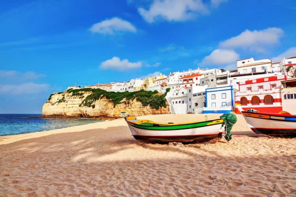 fishing boats on a beach in front of colourful houses at Carvoeiro, the Algarve