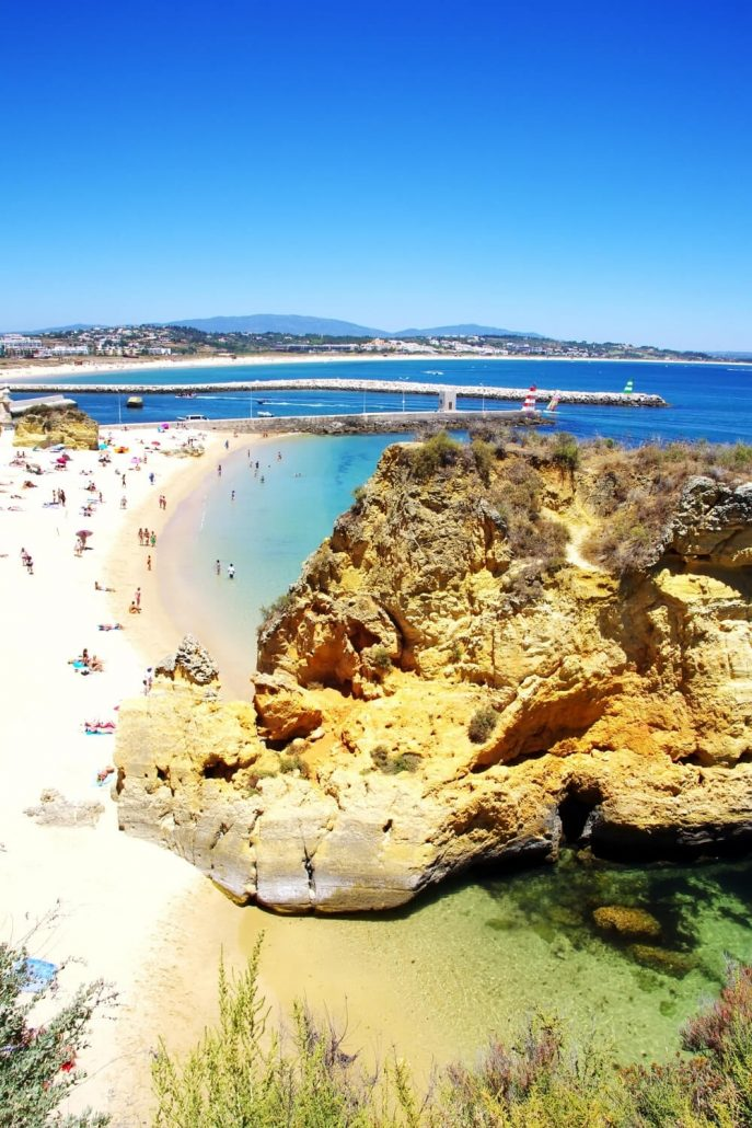 A picture of cliffs leading to a golden sandy beach in the Algarve