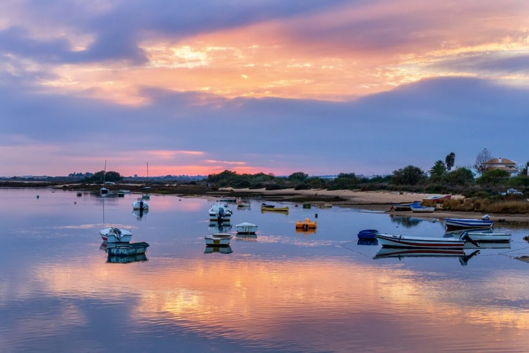 A picture of a purple sunset sky over the calm waters of Cabanas de Tavira with boats on the water
