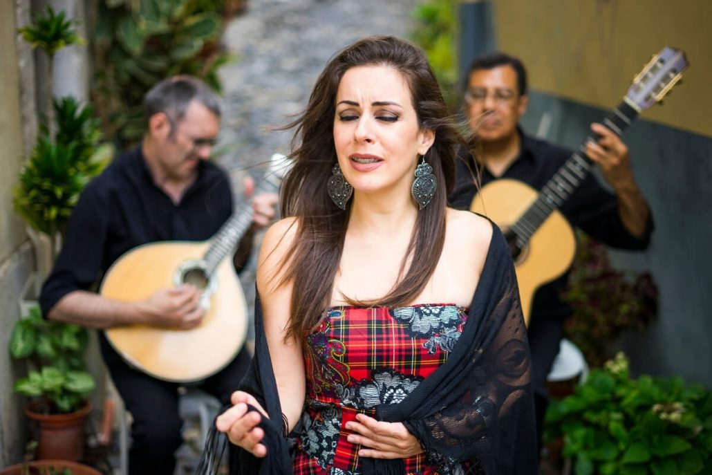 A picture of a Portuguese fado singer with two accompanying guitar players in the background