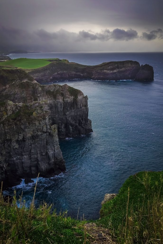 A picture of rocky sea cliffs under a grey, moody sky in the Azores Islands, Portugal