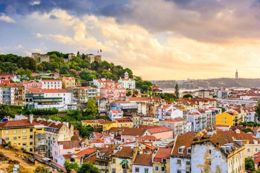 A picture of the hills of Lisbon with the castle to the left and in the distance on the right, the statue of Christ across the river