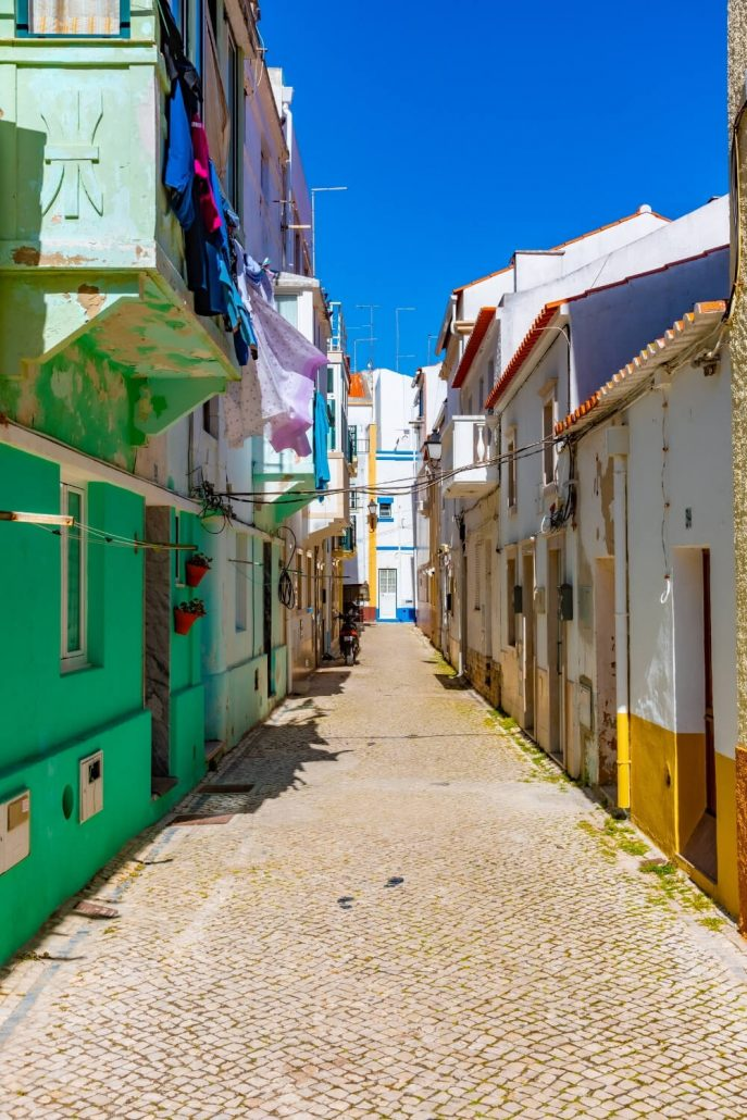 A picture of narrow cobbled streets in Nazare with colourful walls and surrounds of doors and windows.